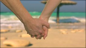 Couple holding hands in lock with tropical resort and ocean on background. Cropped view of people holding hands stock video footage