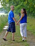 Couple holding hands looking back Royalty Free Stock Photography