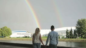 A couple holding hands and looking at two rainbows. stock video footage