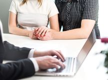 Couple holding hands in meeting with professional man. stock photography