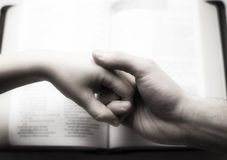 Couple holding hands over bible. Man and woman holding hands closeup, holding each other over a bible. Vintage look with black and white, overexposure, grain and Stock Image