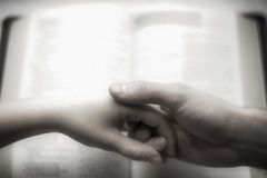 Couple holding hands over bible signalling commitment. Couple holding hands over a bible in the background. Vintage look with black and white, overexposure Royalty Free Stock Photo