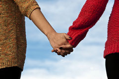 Couple holding hands over blue background stock photo