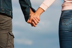 Couple holding hands over blue sky background Stock Photo