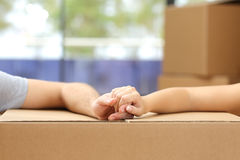 Couple holding hands over a box moving home. Close up of a couple holding hands over a carton box and moving home Stock Image