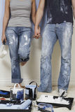 Couple Holding Hands With Painting Tools In Foreground Royalty Free Stock Photography