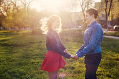Couple holding hands in a park at sunset Royalty Free Stock Images