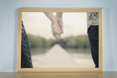 Couple holding hands in the picture frame placed on wood table. Stock Photo