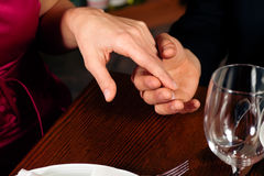 Couple holding hands on a restaurants table. Couple, just hands to be seen, is holding hand while waiting for their food and drinks in a restaurant Stock Images