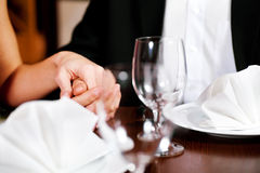 Couple holding hands on a restaurants table. Couple, just hands to be seen, is holding hand while waiting for their food and drinks in a restaurant Royalty Free Stock Images