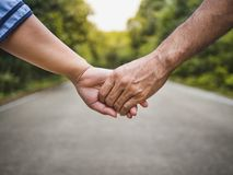 Couple holding hands on the road and forest blurred background. stock images