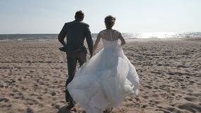 Couple holding hands running on the beach, camera movement