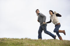Couple Holding Hands And Running In The Park Stock Images