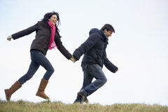 Couple Holding Hands And Running In The Park Royalty Free Stock Image