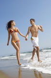 Couple Holding Hands While Running In Surf At Beach. Young loving couple holding hands while running in surf at beach Royalty Free Stock Photo