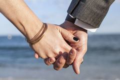 A couple holding hands by the sea. A couple grabbing each others hands with the mediterranean blue sea as background. The focus is on a hands Stock Images