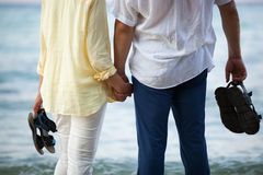 Couple holding hands at the seaside. Man and women standing barefoot by the sea and holding hands. Romantic vacation Stock Image