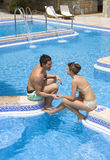 Couple holding hands and sitting at edge of swimming pool.  stock photography