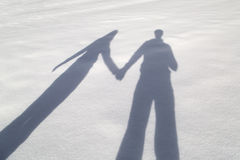 Couple holding hands in snowy walk. Shadows of romantic couple in love on a winter snowy walk. Shadow of men and women holding hands together. Beautiful snowy royalty free stock images