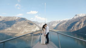 The couple is holding hands and standing head-to-head while travelling on the boat in the mountains. stock video