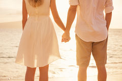 Couple holding hands at sunset on beach Stock Photo