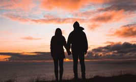 A couple holding hands at sunset by the sea stock photos