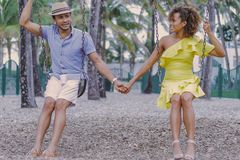 Couple holding hands on swing Royalty Free Stock Images