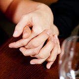 Couple holding hands on a table Royalty Free Stock Image