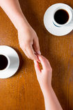 Couple holding hands on the table in the cafe Stock Photography