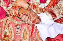 Couple holding hands- taking the marriage oath. Indian Couple holding hands - taking the marriage oath Stock Image