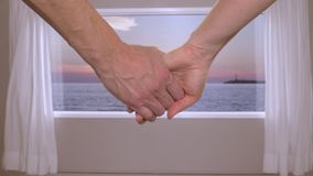 Couple holding hands together in room with beautiful sunset over the sea outside the window. Couple holding hands together in hotel room with beautiful sunset stock footage