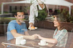 A couple holding hands while waitress serving food Royalty Free Stock Photography