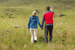 Couple holding hands on walk with man pointing Stock Photography