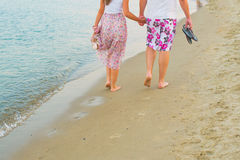 Couple holding hands and walking along the coast Royalty Free Stock Photography