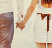 Couple holding hands walking away Stock Photos