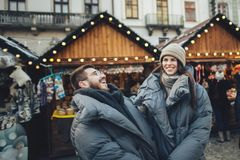 Happy couples on the city square decorated for a Christmas marke Stock Photos