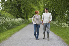 Couple Holding Hands And Walking On Country Road Stock Photos