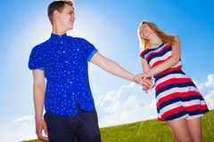 Couple holding hands and walking in green field Stock Photography