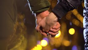 Couple holding hands, walking in night city stock footage