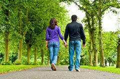 Couple holding hands and walking in a park royalty free stock image
