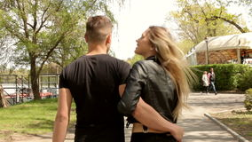 Couple holding hands and walking in park stock video