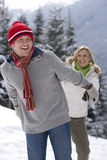 Couple holding hands and walking on remote snowy hillside Stock Photography