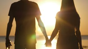 Couple holding hands walking at seaside at sunset stock video