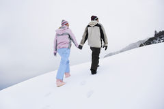 Couple Holding Hands And Walking On Snow Covered Hill Stock Image
