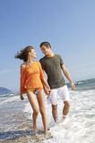 Couple Holding Hands While Walking In Water At Beach Stock Image