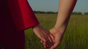 Couple holding hands walkng in field at sunset