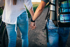 The couple holding hands walks with bicycles stock photo