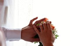 Couple holding hands for a wedding, closeup. Couple holding hands for a wedding on top of white background and pink flowers bouquet, closeup Stock Photos