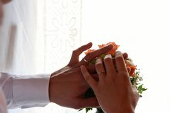 Couple holding hands for a wedding, closeup. Couple holding hands for a wedding on top of white background and pink flowers bouquet, closeup Royalty Free Stock Images