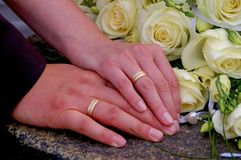 Couple holding hands during wedding with wedding rings and flowers, close-up.  Royalty Free Stock Photography